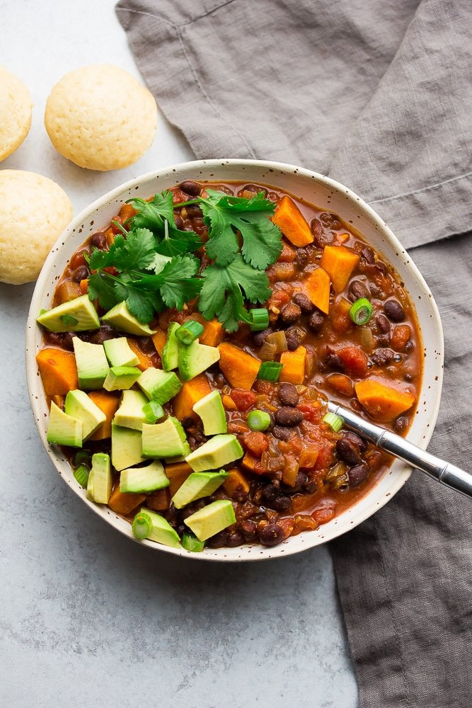 bowl of chili with sweet potatoes, avocado and cilantro on top, grey towel and background