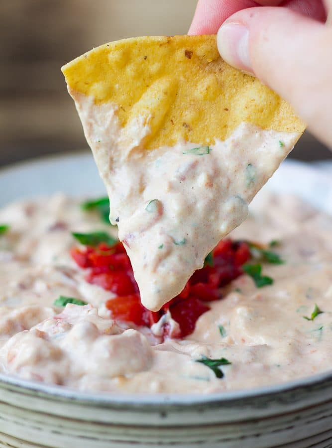 vegan queso in a bowl with chip being dipped into it