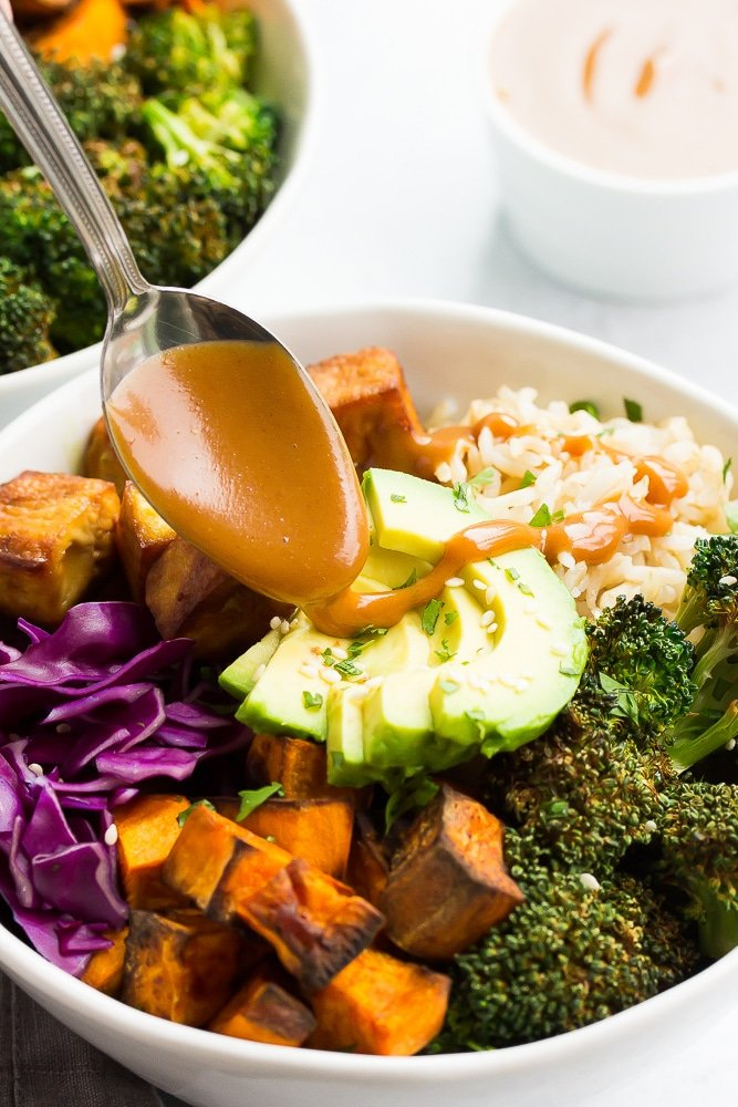 buddha bowl with rice, vegetables and tofu with vegan peanut sauce drizzling on top with a spoon.