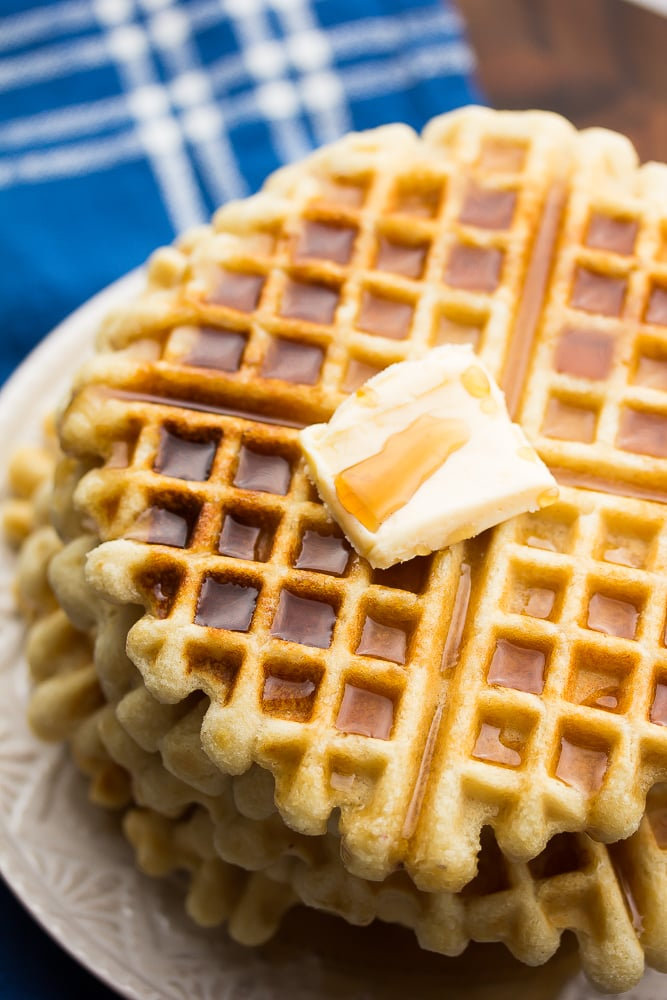 side shot of stack of waffles with syrup and butter