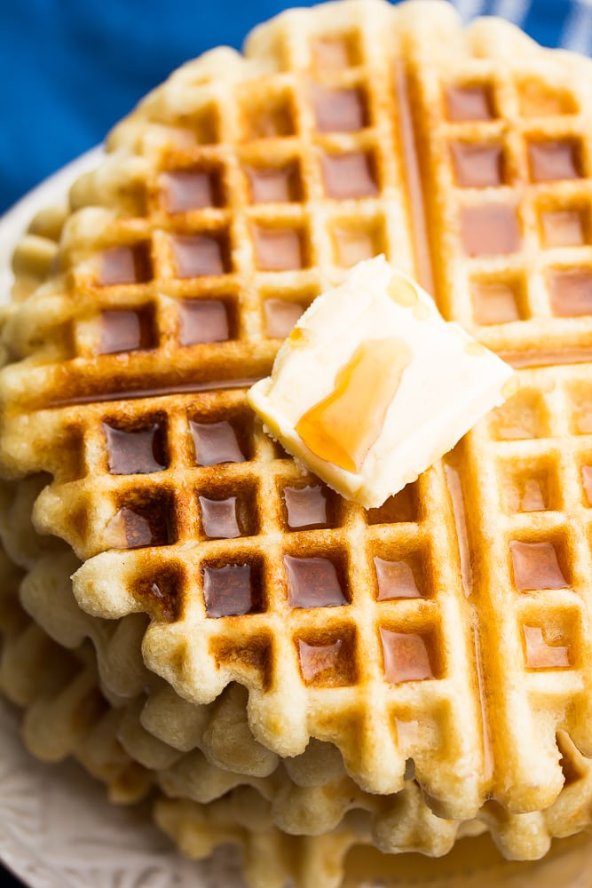 close up of vegan gluten free waffles with blue towel and butter