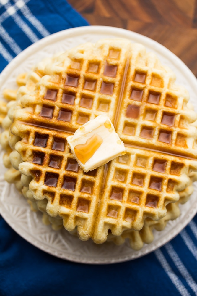 looking down on a plate of waffles with syrup and butter