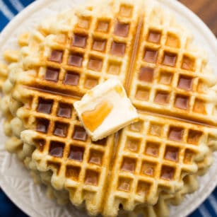 square image of waffles on a plate with butter