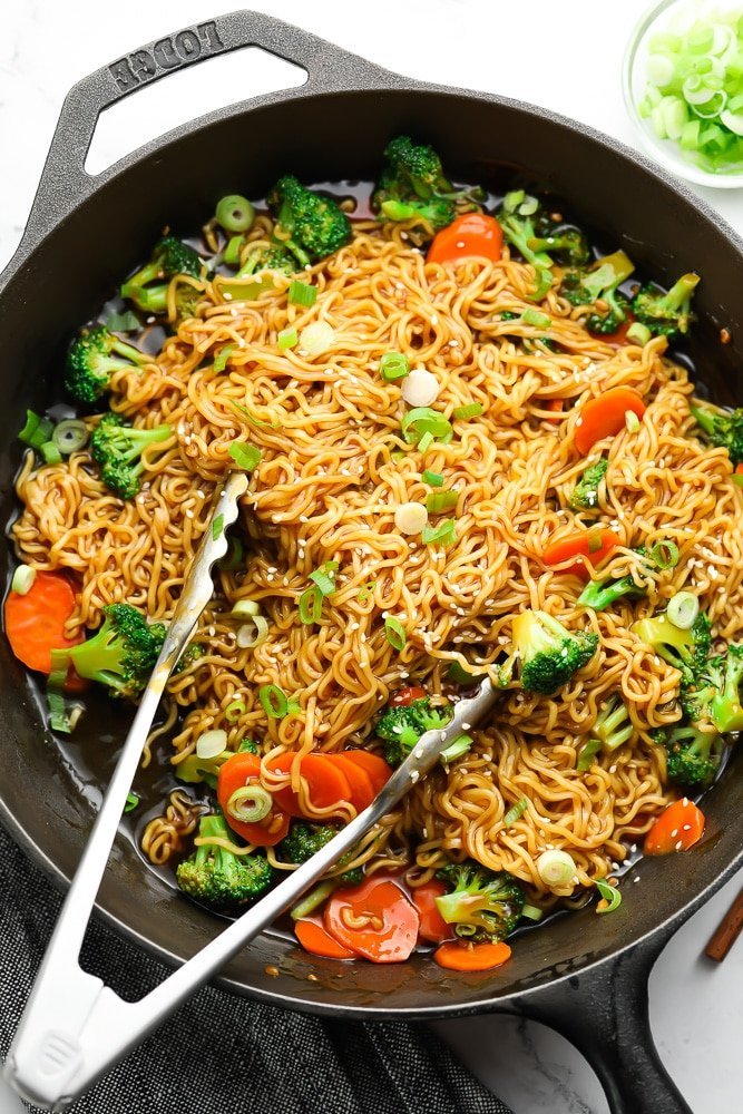 Asian noodles in a pan with tongs