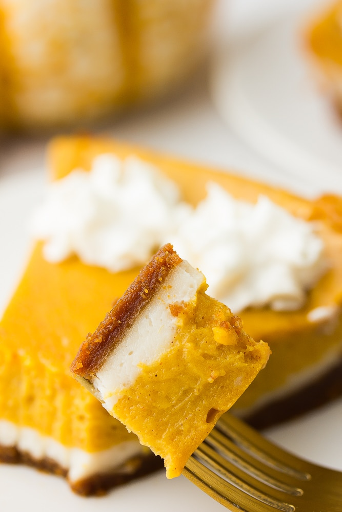 a bite taken of vegan double layered pumpkin cheesecake on a fork