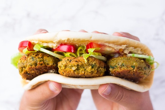 vegan falafel in flatbread with veggies and hands holding it