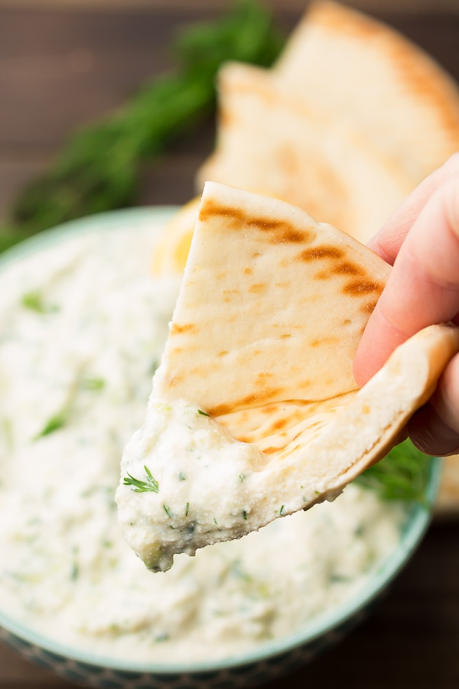 pita bread being dipped into tzatziki