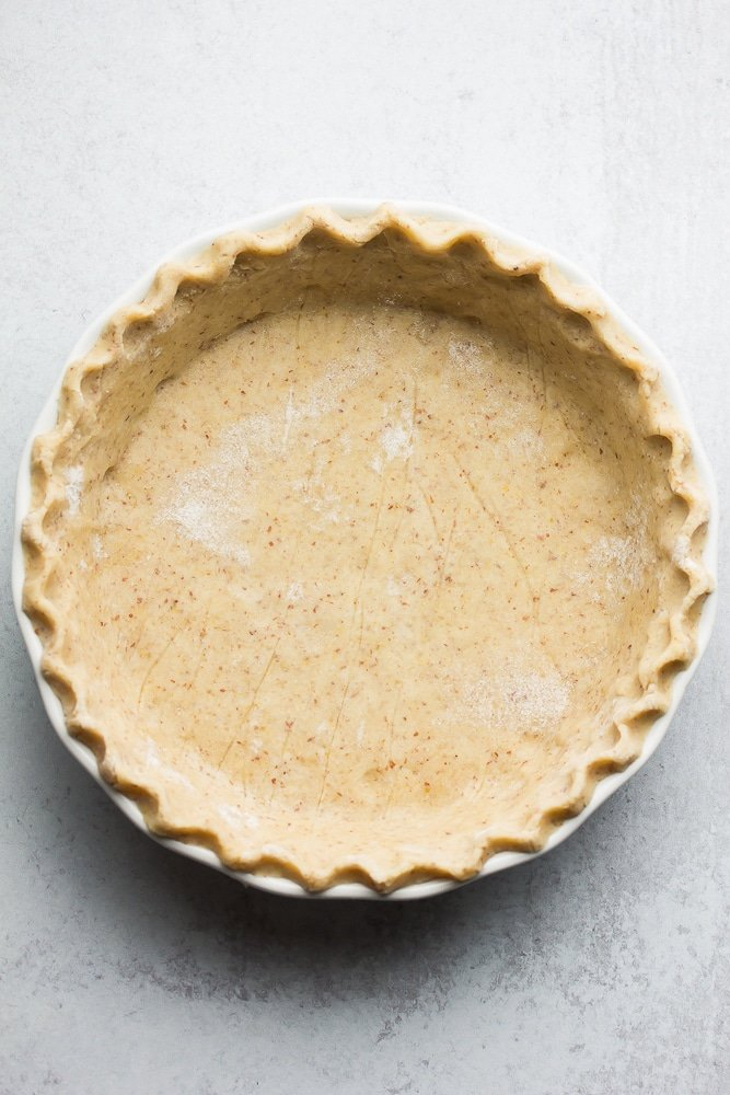 an uncooked healthy pie crust with grey background, nicely in pie pan