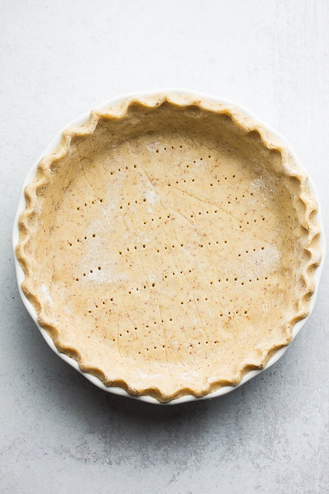 uncooked pie crust with fork holes in it, grey background