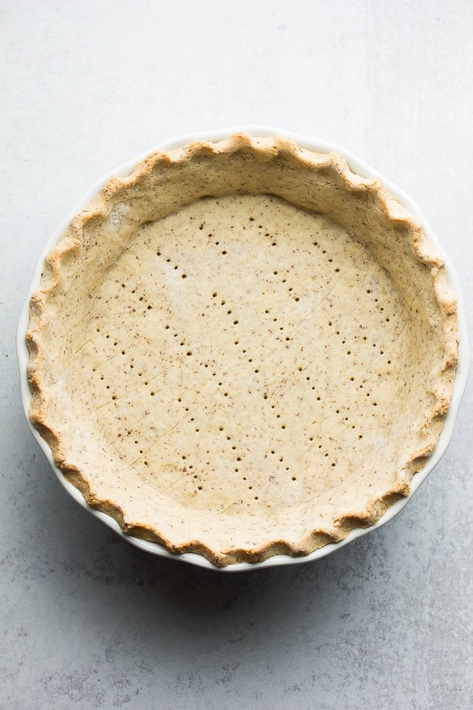 cooked pie crust on a grey background with fork holes