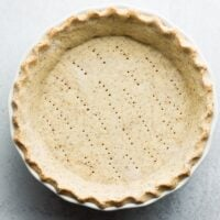 square image of cooked pie crust, fluted edges, fork holes in the middle on a grey background