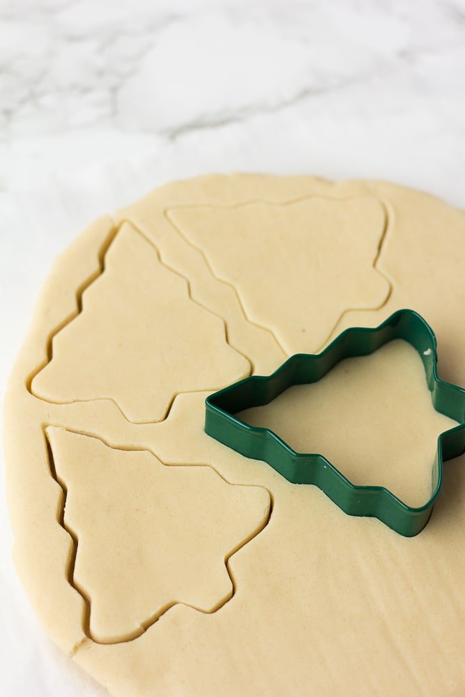 vegan sugar cookies dough being cut with christmas tree cutter