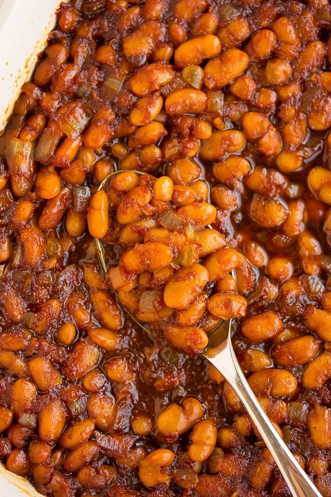 looking down on a dish filled with vegan baked beans and a spoon