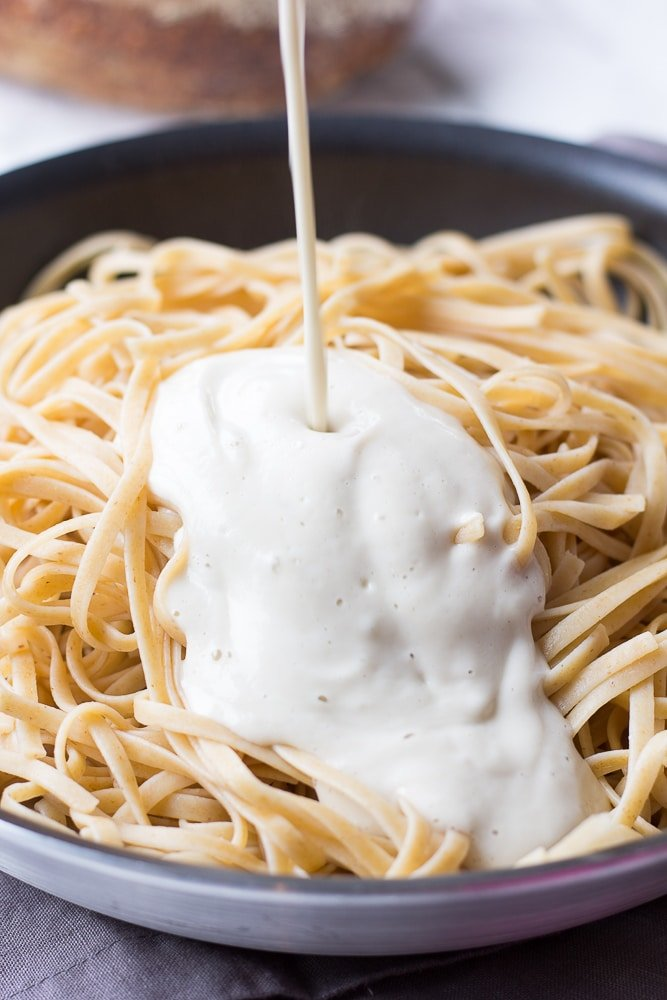 vegan alfredo sauce being poured in a pot of fettucine noodles