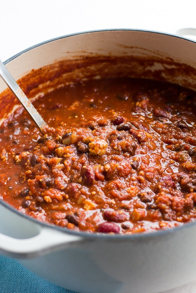 pot of cooked chili with a silver ladle