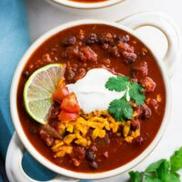 bowl of vegan chili with cashew sour cream, cheese and lime