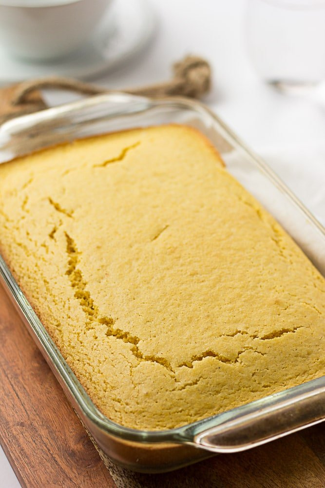 vegan cornbread in a glass pan on a wood cutting board