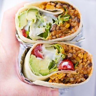 hand holding vegan burrito