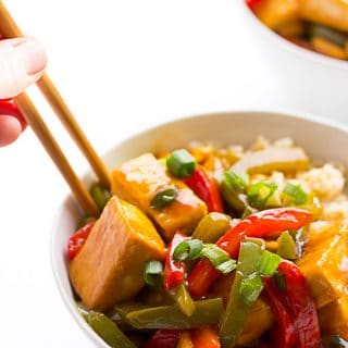 kung pao tofu on top of rice in bowl with chopsticks