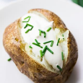 close up of vegan baked potato with vegan sour cream and chives