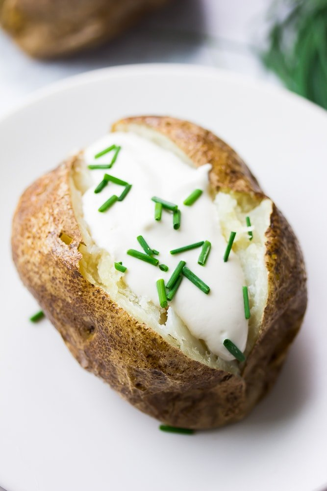 close up of vegan baked potato with sour cream and chives
