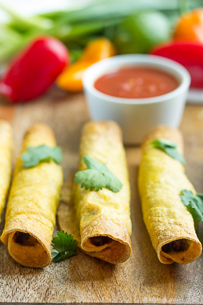 3 taquitos lined up with salsa in the background