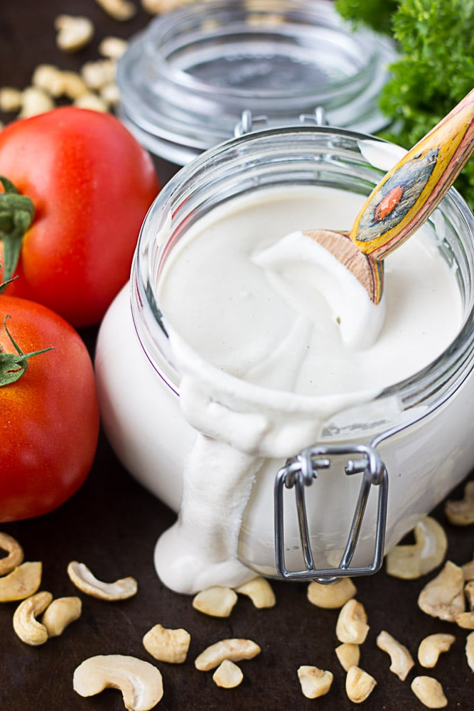 cashew sour cream in a glass dish with tomatoes