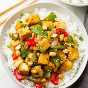 plate with white rice and kung pao tofu and peppers with peanuts on top