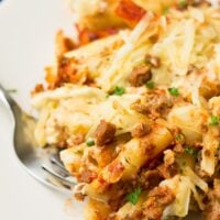 close up of vegan baked ziti on plate with a fork
