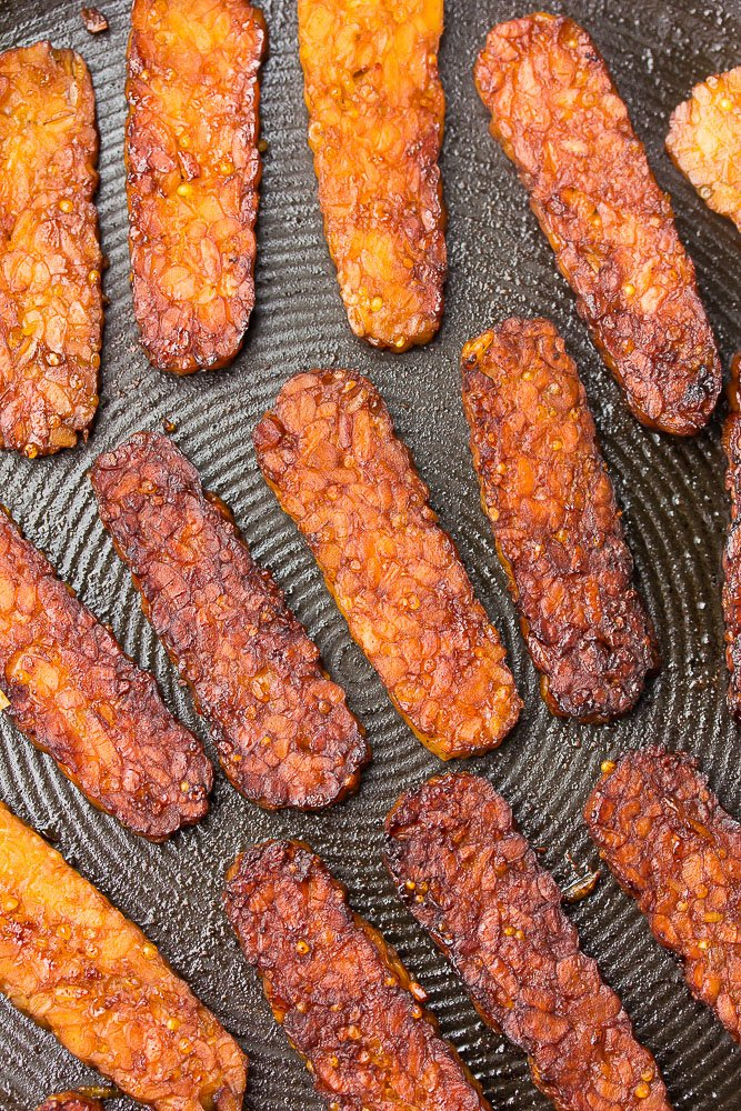 tempeh bacon on a pan being fried