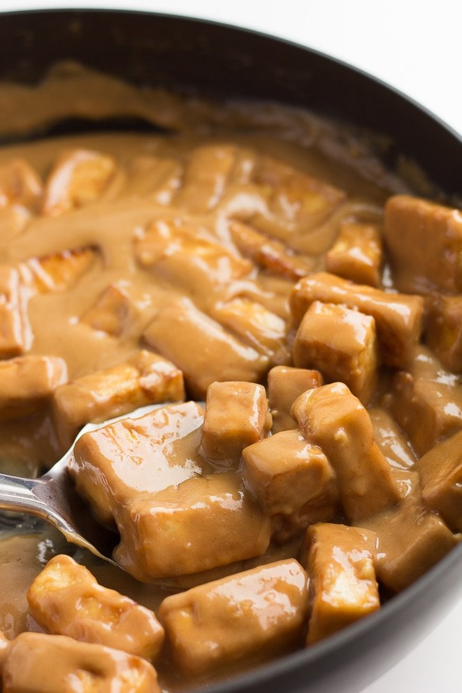 peanut tofu in a pan with a silver spoon