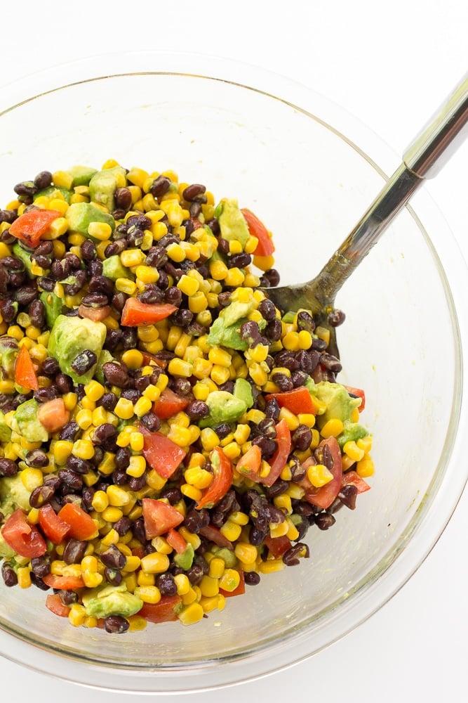 black bean corn avocado salad mixed together in a bowl