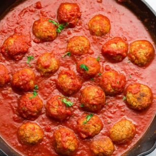 square image of balls in marinara in a cast iron pan
