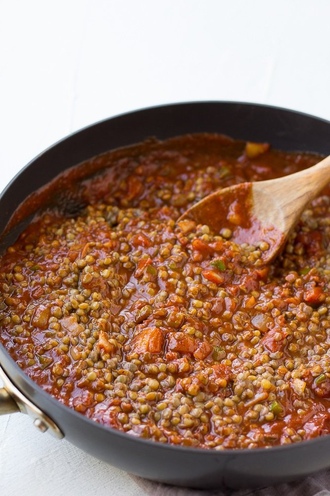 stirring lentils into tomato sauce for vegan sloppy joes