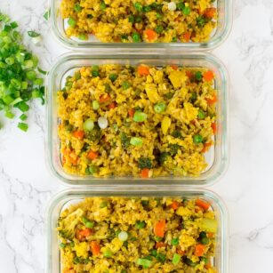 4 glass containers filled with vegan fried rice meal prep dish.