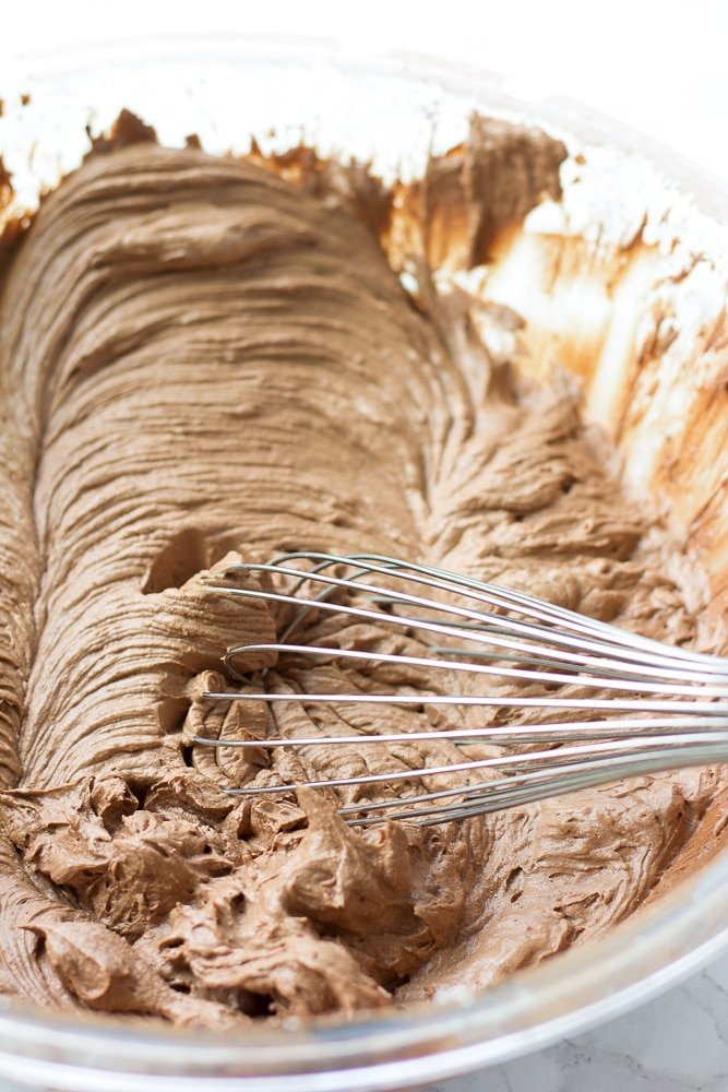 vegan chocolate frosting in a bowl with a whisk