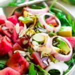 square photo of a salad with avocado and watermelon chunks