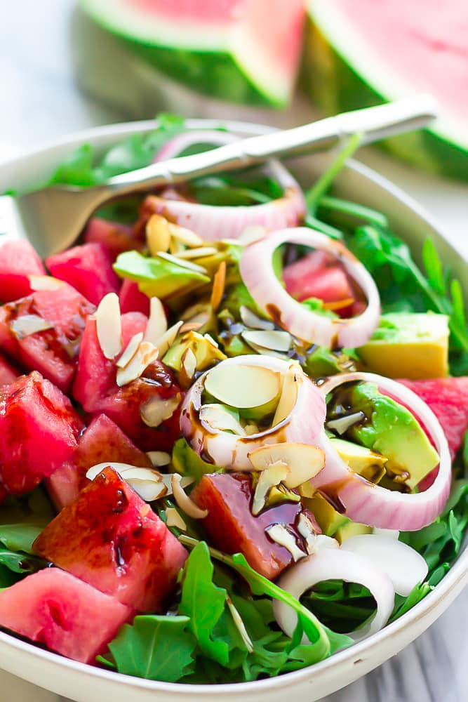 arugula watermelon salad with onions and avocado in a bowl