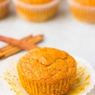 1 vegan pumpkin muffin with cinnamon sticks in the back