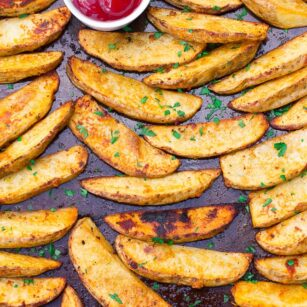 oven roasted potato wedges on a pan with ketchup