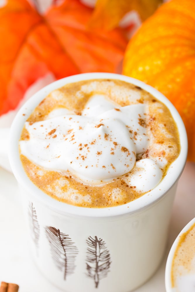 white cup with brown leave with vegan pumpkin spice latte, pumpkins in background