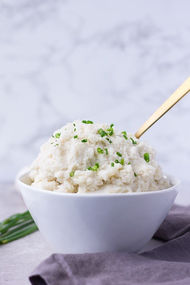 vegan mashed potatoes from the side in a bowl, gray background