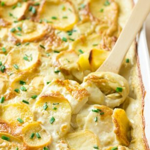 vegan scalloped potatoes in casserole dish with a wooden spoon