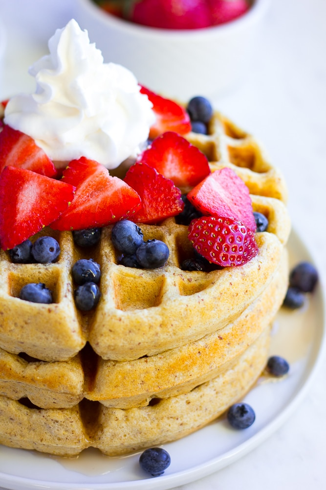 stack of vegan waffles with berries and whip