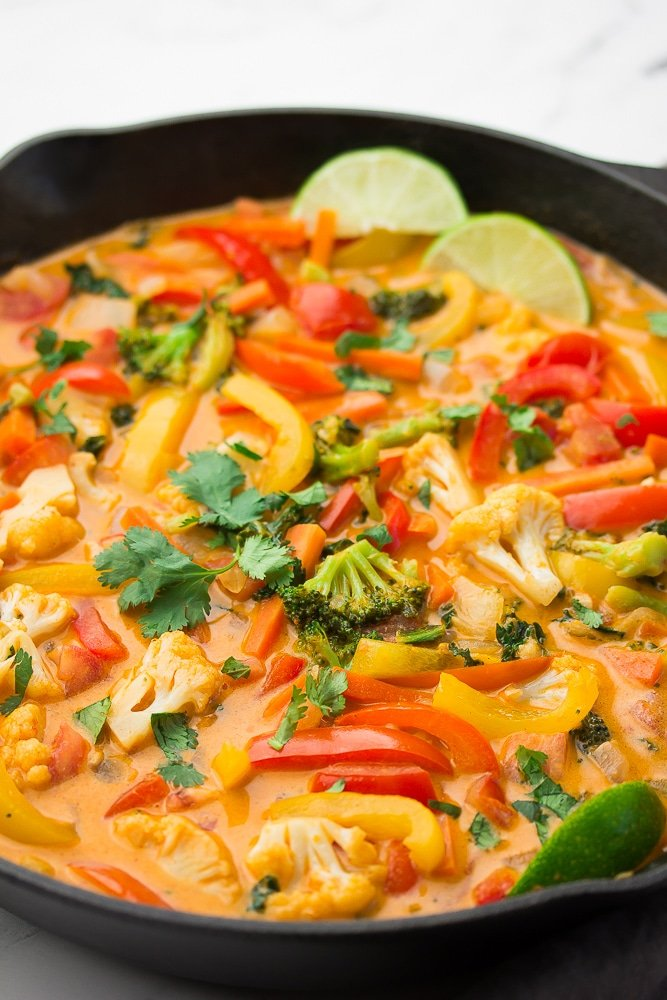 a cast iron pan full of vegetables in creamy red curry sauce