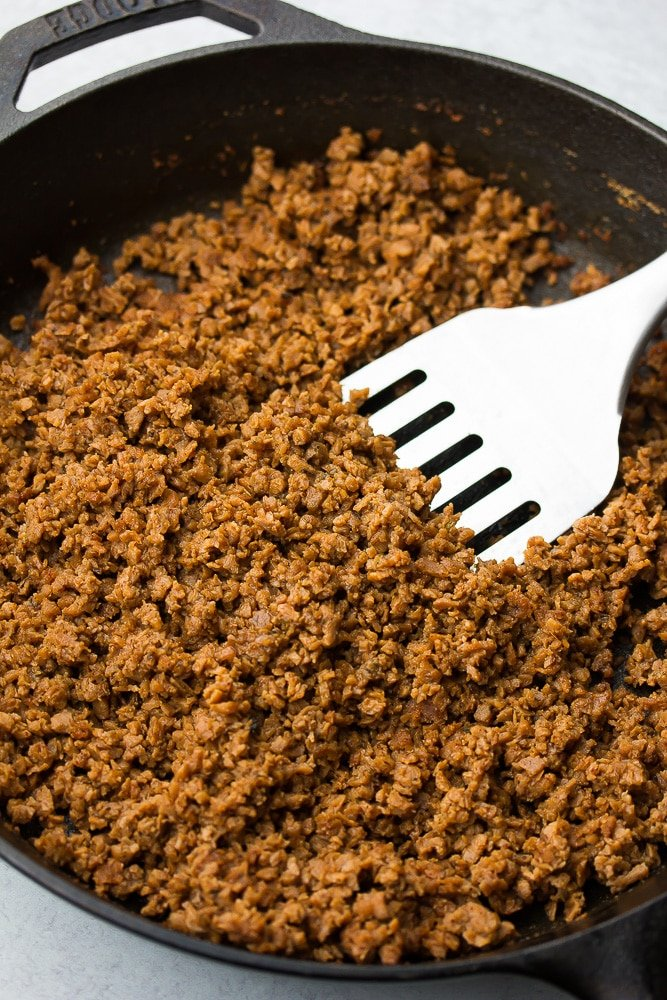 vegan ground taco beef in a black pan with a spatula