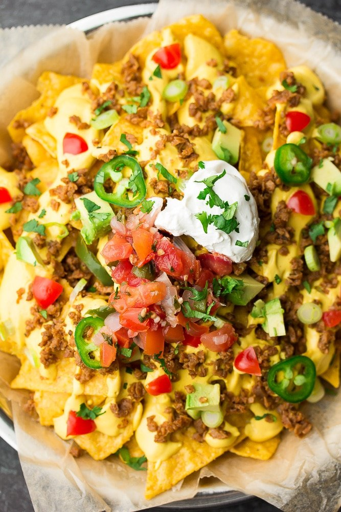 looking down on a plate of nachos with loads of toppings