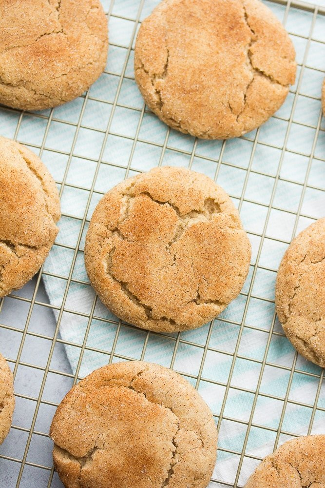 lots of snickerdoodles cookies on a cooling rack