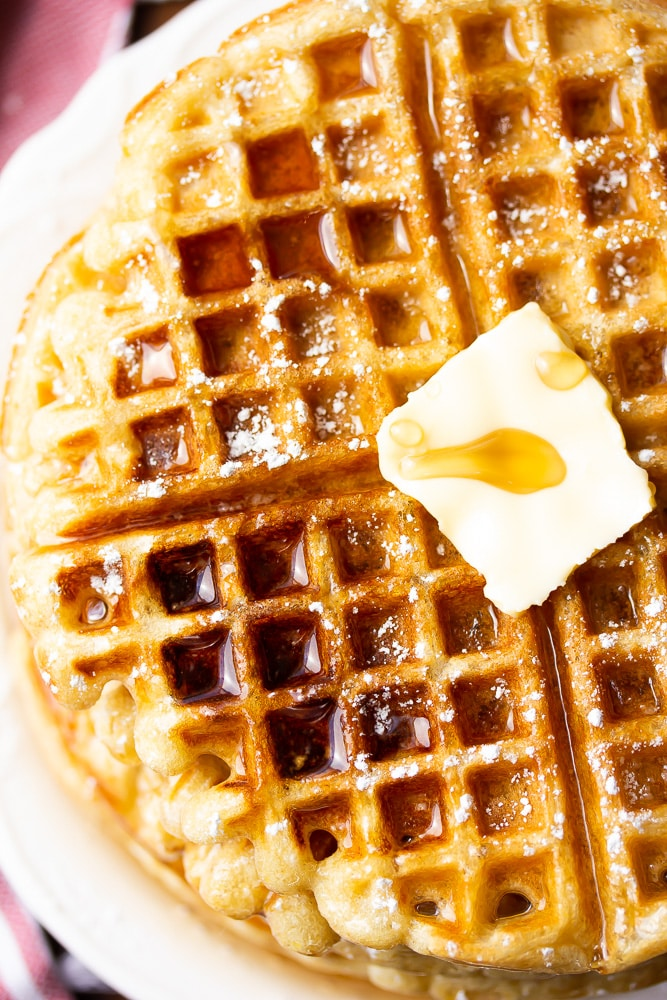 close up of a waffle with butter and syrup all over it