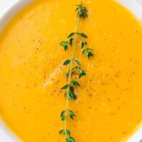 close up of a bowl of instant pot butternut squash soup with thyme
